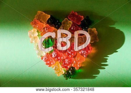 Photo Of Wooden Letters Cbd On A Green Background And Bears Gelatin In The Form Of Heart. View From