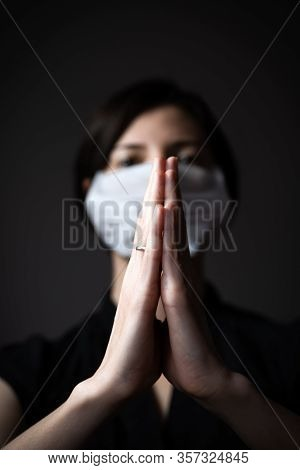 Closeup Hands Of Praying Adult Woman Wearing Hygienic Mask To Prevent Infection, Airborne Respirator