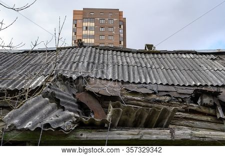 The Roof Of A Partially Destroyed Abandoned Wooden House In The Moscow Region, Russia. Deformed And