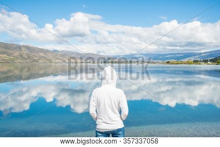 Tourist Standing And Looking To The Spectacular Reflection Of Lake Dunstan In Cromwell, New Zealand.