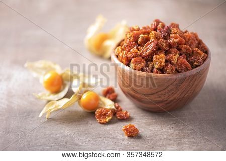 Dried Physalis In Wooden Bowl And Fresh Berries On Wood Textured Background. Copy Space. Superfood,