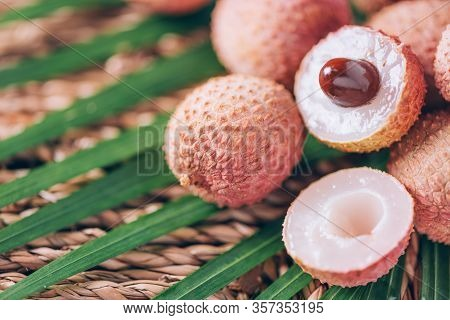 Lychee Fruits With Palm Leaves On Rattan Background. Copy Space. Exotic Litchi, Lichee Fruits. Tropi