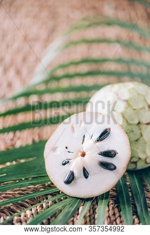 Annona Muricata Or Soursop, Graviola And Guyabano With Palm Leaves On Rattan Background. Copy Space.