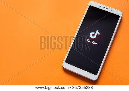 Tver, Russia - February 12, 2020 Tik Tok Logo On Smartphone Screen On Orange Background. Tik Tok Ico