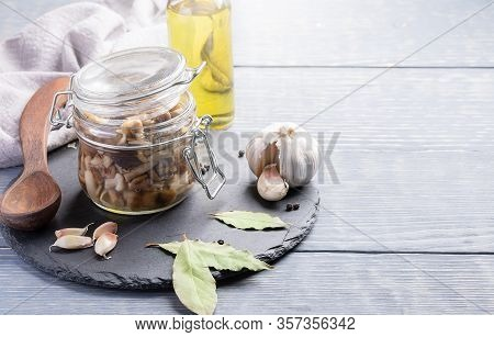 Homemade Pickled Forest Honey Agarics In Glass Jar, Spices, Spoon, Napkin And Oil Bottle On Grey Woo