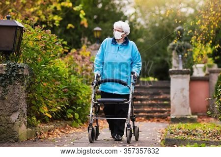 Senior Handicapped Lady Wearing Face Mask With A Walking Disability At Coronavirus Outbreak