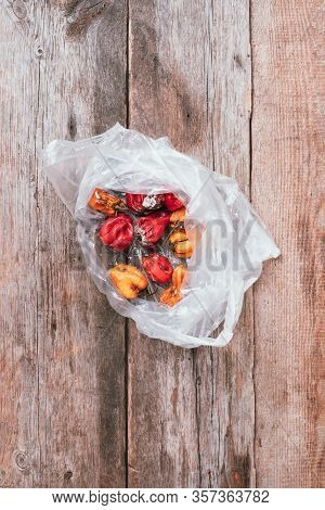Moldy And Wrinkled Rotten Peppers In Plastic Bag On Wooden Background. Concept Of Unhealthy, Decompo