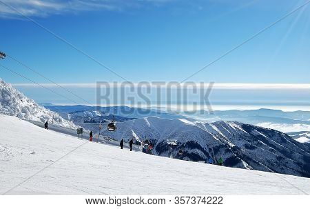 Jasna, Slovakia - January 22, 2019: Cableway, Skiers And Panoramic View On The Mountains Peaks In Lo