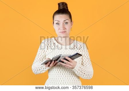 The Girl Holds Four Phones In Her Hands And Looks Inquiringly At The Camera, Depicting The Difficult