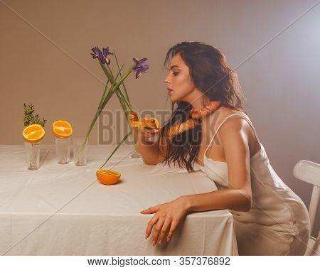 Portrait Of Woman In Studio At White Table With Orange Snake On Her Neck. Model With Predatory Snake