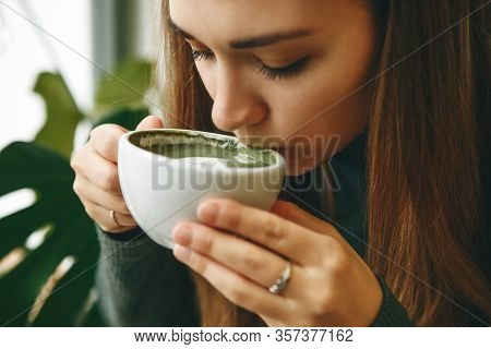 Close-up Face Or Portrait Of A Girl Who Drinks Healthy And Delicious Green Matcha Latte Tea
