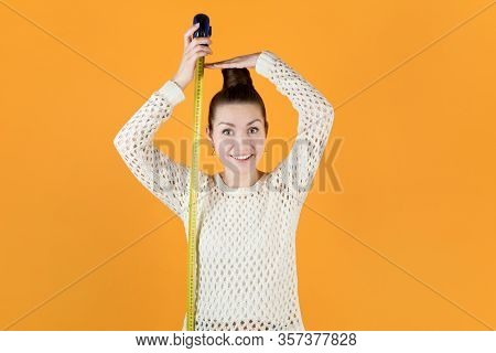 Smiling Girl Holds Measuring Tape Next To Her And Measures Her Height, Isolated On Orange-yellow