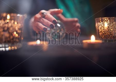 Close-up of fortuneteller in green dress divining on magic ball table with burning candles