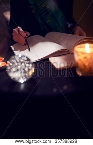 Close-up of fortuneteller hands, predictions books, predictions ball on black table