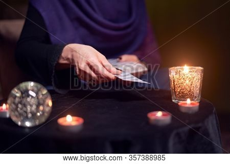 Fortuneteller woman divines on cards sitting at table with burning candles