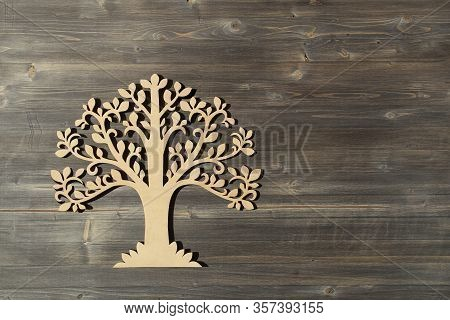Laser Cut Wood Tree Ornament On Wooden Background.  Wooden Tree Symbol On Wood Texture With Copy Spa