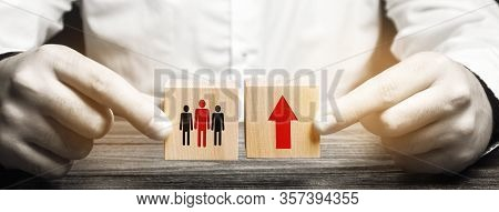 A Man Holds Wooden Blocks With The Image Of People And A Red Up Arrow. The Concept Of Population Gro