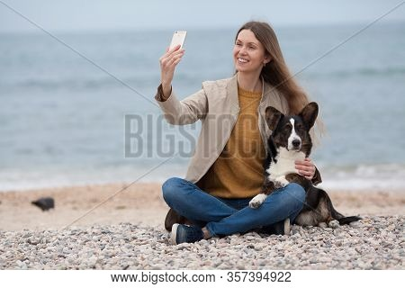 Owner Of A Beautiful Girl With Her Dog Welsh Corgi Cardigan Sitting On The Beach Taking A Selfie On