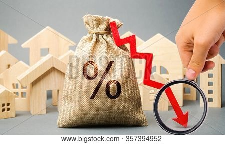 Money Bag With Percents, Down Arrow And Miniature Houses. The Concept Of Low Interest Rates On Mortg