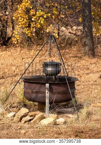 Stew cooking in a cast iron potjie suspended over open fire in a fire pit outdoors; with fall color background