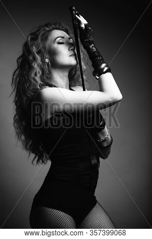 Beautiful Sexy Domineering Woman Holding A Whip In Her Hands And Kissing Him. She Is Wearing A Corse