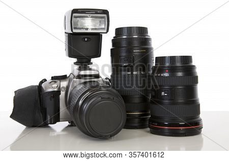 A Digital Slr Camera And Lenses Against A White Background.