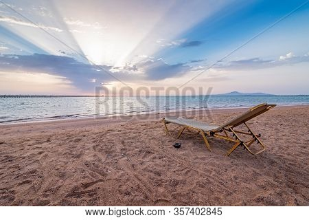 Beautiful Sunset On An Empty Tropical Beach. Lonely Sunbed On Beach Of Red Sea, Egypt. The Sea Coast