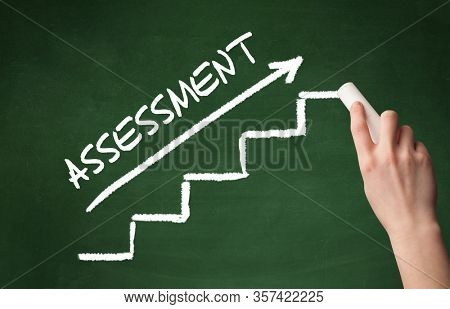 Hand drawing ASSESSMENT inscription with white chalk on blackboard, business concept