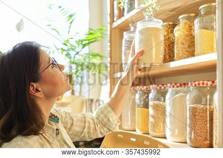 Mature Woman In The Kitchen Pantry With Products. Storage Wooden Stand With Kitchenware, Products Ne