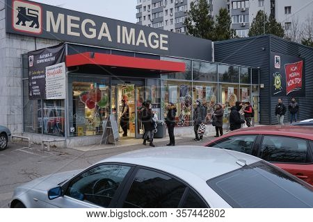 Bucharest, Romania - March 24, 2020: People Wait In Line In Front Of A Mega Image Supermarket, Keepi
