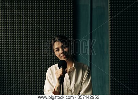 young woman with mic in music studio