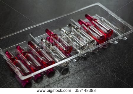 Multi-colored Ampoules With Medicines On A Dark Background. Glass Ampoules With Vitamins B1, B6 And