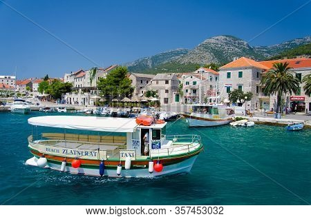 Brac, Croatia - May 17, 2016: Colourful Taxi Boat In Water Of Marina Bol Port Of Pain In Front Of Ol