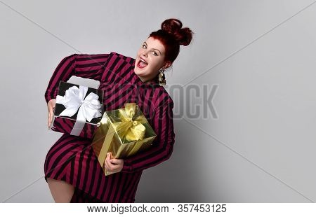 Obese Redhead Lady In Black And Purple Striped Dress And Earrings. Holding Golden And Silver Gift Bo
