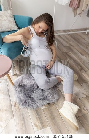 Young Pregnant Woman Relaxing At Home, Expecting Her Baby, Holding A Clock - Countdown To A Delivery