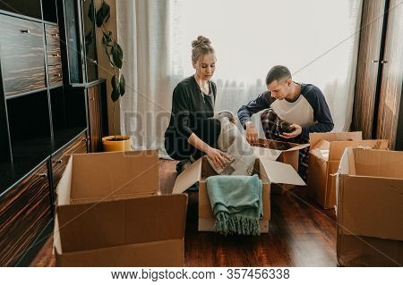 Couple Holding Moving Boxes In New Home. Moving Day, New Home, Unpacking Boxes, Newlyweds Concept