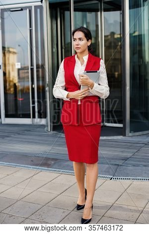 Young Successful Business Woman Dressed In Luxury Formal Wear Holding Touch Pad While Standing Outsi