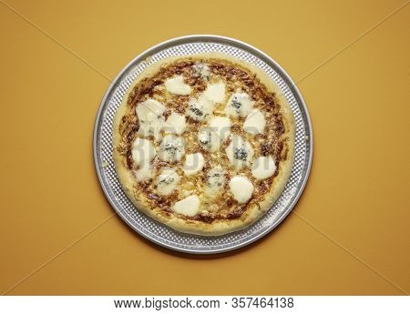 Quattro Formaggi Pizza On A Metal Baking Tray On Orange Seamless Background. Whole Four Cheese Pizza