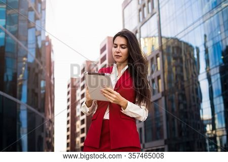 Successful Woman Professional Real Estate Analyst Using Applications On Modern Touch Pad While Stand