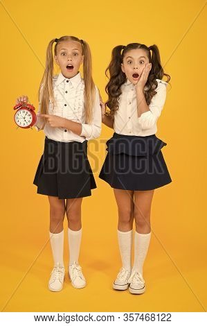 Omg. Got A Surprise. Surprised Schoolgirls Checking Time On Yellow Background. Shocked Little Childr