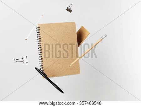 Stationery Set. Levitation Of Notepad, Pencils, Pen, Sticker And Binder Clips. Copy Space On Noteboo
