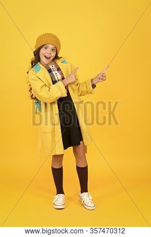 Look At Closely. Surprised Child In Autumn Fashion Pointing At Something. Small Schoolgirl With Open