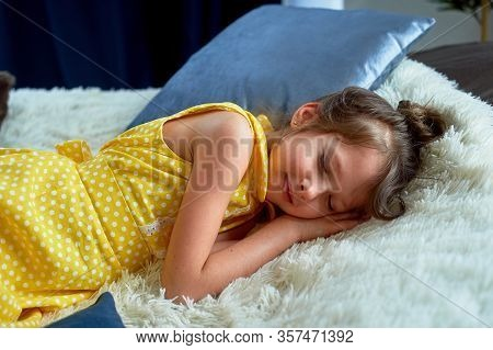 A 6-year-old Girl In A Yellow Dress. I Fell Asleep With My Clothes On. Fatigue From Playing And Brai