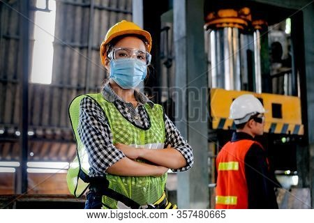 Factory Woman Worker Or Technician With Hygienic Mask Stand With Confident Action With Her Co-worker