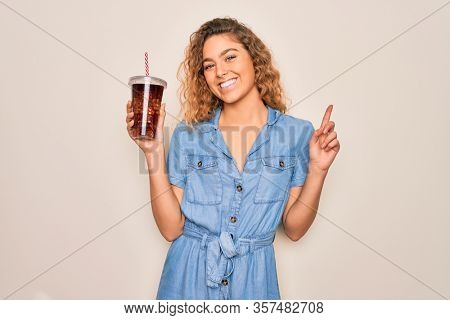 Beautiful blonde woman with blue eyes drinking cola beverage using straw to refreshment surprised with an idea or question pointing finger with happy face, number one