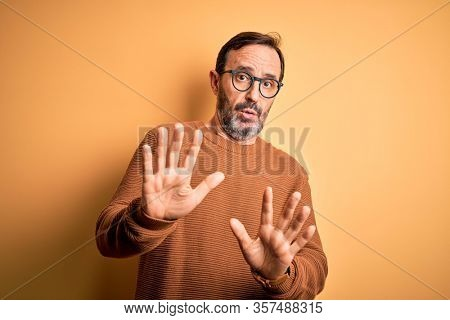 Middle age hoary man wearing brown sweater and glasses over isolated yellow background Moving away hands palms showing refusal and denial with afraid and disgusting expression. Stop and forbidden.