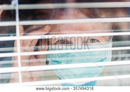 Photo Of Elderly Woman With Medical, Surgical Mask On Her Face Peaking Through The Window From Insid
