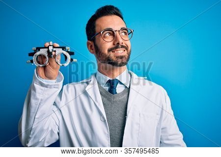 Young handsome optical man with beard holding optometry glasses over blue background smiling looking to the side and staring away thinking.