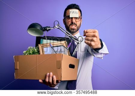 Young handsome businessman with beard holding cardboard box with fired reminder on head annoyed and frustrated shouting with anger, crazy and yelling with raised hand, anger concept