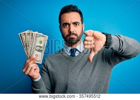 Young handsome man with beard holding bunch of dollars banknotes over blue background with angry face, negative sign showing dislike with thumbs down, rejection concept